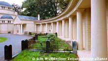 31.07.2000, Berlin /Treptow : Das Treptower Hochbauamt ließ die denkmalgeschützte Feierhalle auf dem Altglienicker Friedhof sanieren . Der Friedhof in Altglienicke wurde 1911 als städtische Begräbnisstätte angelegt. An der Schönefelder Chaussee fanden vor allem Bewohner der nahe liegenden Siedlungen ihre letzte Ruhe. Die Pläne für die Friedhofskapelle stammen von dem Architekten K.A. Hermann. Er war 1910 von der Gemeinde Niederschöneweide mit dem Bau für eine Feierhalle mit 120 Sitzplätzen beauftragt worden. Das Gebäude, an das er links und rechts Kolonnaden baute fällt vor allem wegen seiner Kuppel und seiner Säulen im italienischen Baustil auf. Die Sanierung und Erneuerung kosteten rund 943000 Mark. Foto: Rekonstruierter Städtischer Friedhof an der Schönefelder Chaussee 1oo. Blick auf die Kolonnaden, links die Friedhofskapelle. Vor dem Ensemble fanden angesehene Altglienicker Bürger ihre letzte Ruhe in Erbbegräbnissen.