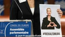Tatiana Khomich holds a poster of jailed Belarus civil rights activist Maria Kalesnikava who won the Vaclav Havel Human Rights Prize awarded at the Parliamentary Assembly of the Council of Europe in Strasbourg, eastern France, Monday, Sept. 27, 2021. (AP Photo/Jean-Francois Badias)