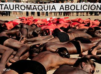 Activists hold a banner reading ''Abolish bullfighting'', as people cover their bodies with red and black during a protest