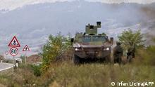 Serbian army soldiers stand guard by their armoured vehicles in the village of Rudnica near the southern Serbian town of Raska on September 27, 2021, where tensions are high at the border between Kosovo and Serbia as Belgrade deployed four armoured vehicles close to the frontier, an AFP correspondent saw. - Already tense relations between Serbia and its former ethnic-Albanian majority province have grown worse since the government in Kosovo despatched special police units to the north a week ago, an area mainly populated by ethnic Serbs who reject the authority of Pristina. The move, which angered the Serbs, came after Pristina decided to require drivers with Serbian registration plates to put on temporary ones when entering Kosovo. (Photo by Irfan LICINA / AFP)
