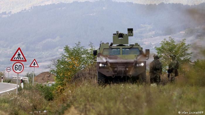 Serbische Soldaten stehen neben ihrem gepanzerten Fahrzeug an der Grenze zum Kosovo