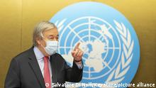UN Secretary-General Antonio Guterres arrives for a press conference wearing a face mask, next to the UN logo