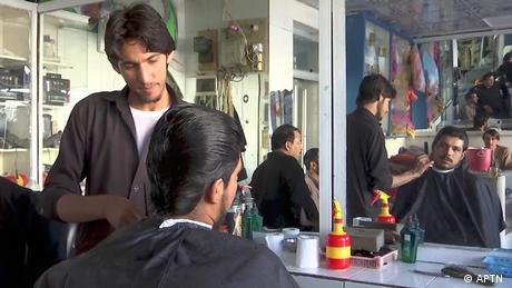 Bilal Ahmad, a resident of Lashkar Gah, is having his hair cut.
