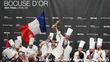 French chef Davy Tissot, center, celebrates with his teammates after winning the Bocuse d'Or (Golden Bocuse) trophy, in Lyon, central France, ahead Denmark team members, left, who finished second, and Sweden team members, right, who came third, Monday, Sept. 27, 2021. The contest, a sort of world cup of cuisine, was started in 1987 by Lyon chef Paul Bocuse to reward young international culinary talents. (AP Photo/Laurent Cipriani)