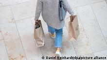 27.09.2021, Hamburg - Eine Frau geht mit zwei Einkaufstüten durch ein Einkaufszentrum.