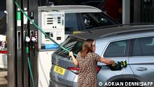 A member of the public fills up her car at a Tesco petrol station in Camberley, west of London on September 26, 2021. - Britain's transport secretary Grant Shapps on Sunday accused lorry industry representatives of helping to spark petrol panic-buying, as he defended a U-turn on post-Brexit immigration policy to ease an escalating supply crisis. (Photo by Adrian DENNIS / AFP)