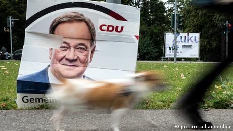 Auf einer Wiese am Straßenrand steht schräg und angerissen ein Wahlplakat der CDU mit dem Porträt von Armin Laschet