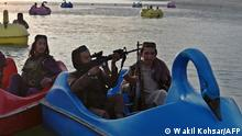 In this photograph taken on September 28, 2021 Taliban fighters ride on paddle boats at Qargha Lake on the outskirts of Kabul. - This is Afghanistan! a Taliban fighter shouts on the pirate ship ride at a fairground in western Kabul, as his armed comrades cackle and whoop on board the rickety attraction. (Photo by WAKIL KOHSAR / AFP) / TO GO WITH: Afghanistan-conflict-fairground, SCENE by James EDGAR