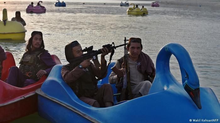 A man with a machine gun rides a paddle boat