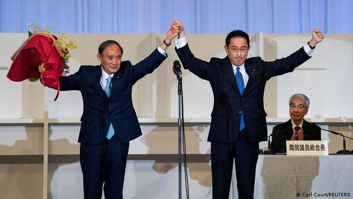 Fumio Kishida (r.) und Yoshihide Suga (l.) stehen auf einer Bühne und halten triumphierend die Fäuste in die Luft, Yoshihinde Suga hält dabei einen Blumenstrauß in der linken Hand und die Hand Kishidas in seiner rechten.
