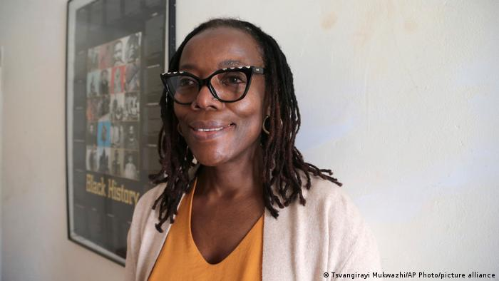 Tsitsi Dangarembga: Woman smiles into camera, poster on a wall in the background