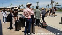 Passengers arriving on a flight from the United Kingdom walk at Faro airport, outside Faro, in Portugal's southern Algarve region, Monday, May 17, 2021. British vacationers began arriving in large numbers in southern Portugal on Monday for the first time in more than a year, after governments in the two countries eased their COVID-19 pandemic travel restrictions. (AP Photo/Ana Brigida)