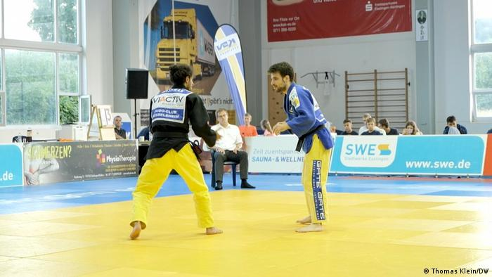 Nashwan squares off with an opponent as an official and several spectators look on