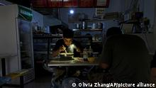 29/09/2021 A man uses his smartphone flashlight to light up his bowl of noodles as he eats his breakfast at a restaurant during a blackout in Shenyang in northeastern China's Liaoning Province, Wednesday, Sept. 29, 2021. People ate breakfast by flashlight and shopkeepers used portable generators Wednesday as power cuts imposed to meet official conservation goals disrupted manufacturing and daily life. (AP Photo/Olivia Zhang)