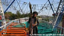 TOPSHOT - In this photograph taken on September 28, 2021 a Taliban fighter carrying a rocket propelled grenade (RPG) launcher stands on pirate ship ride in a fairground at Qargha Lake on the outskirts of Kabul. - This is Afghanistan! a Taliban fighter shouts on the pirate ship ride at a fairground in western Kabul, as his armed comrades cackle and whoop on board the rickety attraction. - TO GO WITH: Afghanistan-conflict-fairground, SCENE by James EDGAR (Photo by WAKIL KOHSAR / AFP) / TO GO WITH: Afghanistan-conflict-fairground, SCENE by James EDGAR (Photo by WAKIL KOHSAR/AFP via Getty Images)