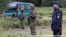 Ein polnischer Polizist und Grenzschutzbeamte stehen an der polnisch-belarussischen Grenze in der Nähe des Ortes Usnarz Gorny im Nordwesten Polens. Nach Angaben des polnischen Grenzschutzes harrt eine Gruppe von 24 Flüchtlingen seit Tagen in der Nähe des Dorfes Usnarz Gorny im Grenzgebiet zu Belarus aus. Laut der Nachrichtenagentur PAP soll es sich um Afghanen handeln. Polen treibt den Bau eines Zauns an der Grenze zu Belarus voran, um sich vor einem Andrang von Migranten aus Krisengebieten, die über Belarus in die EU wollen, zu schützen. +++ dpa-Bildfunk +++