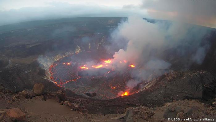 Clouds of gas rise from the crater of the Kilauea volcano as lava is visible in cracks