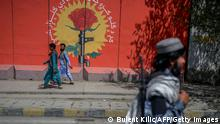 TOPSHOT - A Taliban fighter walks past a mural along a street in Kabul on September 15, 2021. (Photo by BULENT KILIC / AFP) (Photo by BULENT KILIC/AFP via Getty Images)