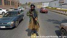 A Taliban fighter stands guard along a street near the Zanbaq Square in Kabul on September 23, 2021. (Photo by WAKIL KOHSAR / AFP) (Photo by WAKIL KOHSAR/AFP via Getty Images)