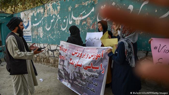 Homem fala com mulheres que carregam faixa, todos de trajes islâmicos. Dedos cobrem parte da tela