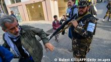 30.09.21 *** A member of the Taliban special forces pushes a journalist (L) covering a demonstration by women protestors outside a school in Kabul on September 30, 2021. (Photo by BULENT KILIC / AFP) (Photo by BULENT KILIC/AFP via Getty Images)
