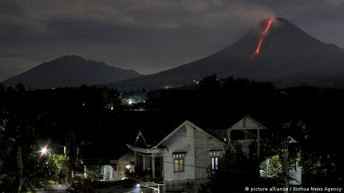 Indonesia's Mount Merapi is visible in the background behind homes, a cataract of lava