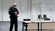 A judicial officer looks at his watch prior to a trial against a 96-year-old former secretary for the SS commander of the Stutthof concentration camp at the court room in Itzehoe, northern Germany, on September 30, 2021. - The woman failed to turn up for the start of her trial, the judge said, issuing an arrest warrant for the fugitive. (Photo by Markus Schreiber / POOL / AFP) (Photo by MARKUS SCHREIBER/POOL/AFP via Getty Images)