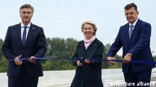 European Commision President Ursula von der Leyen, center, Chairman of the Council of Ministers of Bosnia and Zoran Tegeltija and Prime Minister of Croatia Andrej Plenkovic, left, pose before cutting a ribbon during the inauguration ceremony of the of the Svilaj Bridge, in Donji Svilaj, Bosnia, Thursday, Sept. 30, 2021. The bridge across the Sava river connects Bosnia and Herzegovina and Croatia and is part of a road infrastructure project financed by the European Union. (AP Photo)