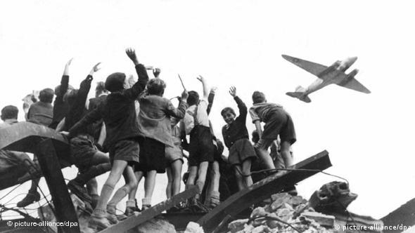 Archive photo of West German children cheering as a Candy Bomber flies overhead