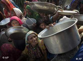 Pakistani women and children wait to be given a fresh meal at a camp for families displaced by floods