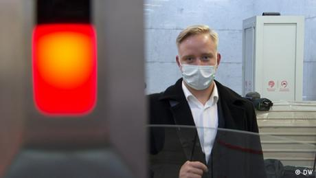 Man with cropped, tidy hair looks forward while wearing a mask and crisp white shirt