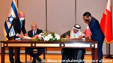 In this photo provided by the Israeli Government Press Office, Israel's Foreign Minister Yair Lapid, left, and his Bahraini counterpart Abdullatif al-Zayani, sign documents during the first high-level visit to the small Gulf state by a senior Israeli official since the signing of a landmark agreement to establish diplomatic ties between the two countries last year, in Manama, Bahrain, Thursday, Sept. 30, 2021. (Shlomi Amshalem/GPO via AP)