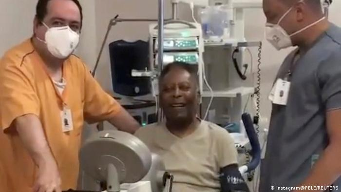 Pele carrying out exercises in Sao Paulo hospital, with two medics