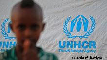 A child stands in front of a UN High Commissioner for Refugees (UNHCR) tent as Ethiopian refugees who fled fighting in Tigray province camp at the Um Raquba camp in Sudan's eastern Gedaref state, on November 19, 2020. - Sudan -- one of the world's poorest countries, now faced with the massive influx -- has reopened the camp, 80 kilometres (50 miles) from the border. It once housed refugees who fled Ethiopia's 1983-85 famine that killed over a million people. (Photo by ASHRAF SHAZLY / AFP)