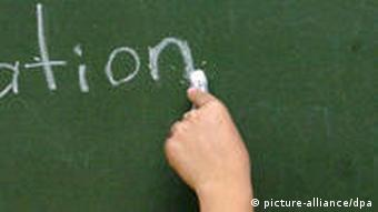 A woman writes 'integration' on a chalk board