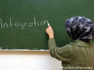 A Muslim schoolgirl writes on a blackboard