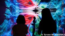 Visitors are pictured in front of an immersive art installation titled Machine Hallucinations - Space: Metaverse by media artist Refik Anadol