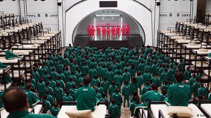 A still from 'Squid Game': a mass of people dressed in green look towards a stage where people dressed in pink stand.