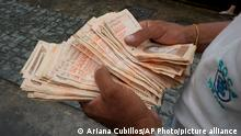 FILE - In this Aug. 5, 2021 file photo, a man counts Bolivar bills that amount to $1, at a bus stop in Caracas, Venezuela. A new currency with six fewer zeros debuts Friday, Oct. 1, 2021, in Venezuela, whose currency has been made nearly worthless by years of the world's worst inflation. (AP Photo/Ariana Cubillos,File)