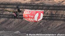 Climate activists entered and stopped a bucket wheel excavator at the Garzweiler open-cast mine near Luetzerath, western Germany, Friday, Oct. 1, 2021. The protestors put a banner reading keep it in the ground. The village of Luetzerath, now almost entirely abandoned as the mine draws ever closer, will be the latest village to disappear as coal mining at the Garzweiler mine expands. (AP Photo/Martin Meissner)