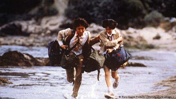 Film still from 'Battle Royale,' bloodied teenagers run through water
