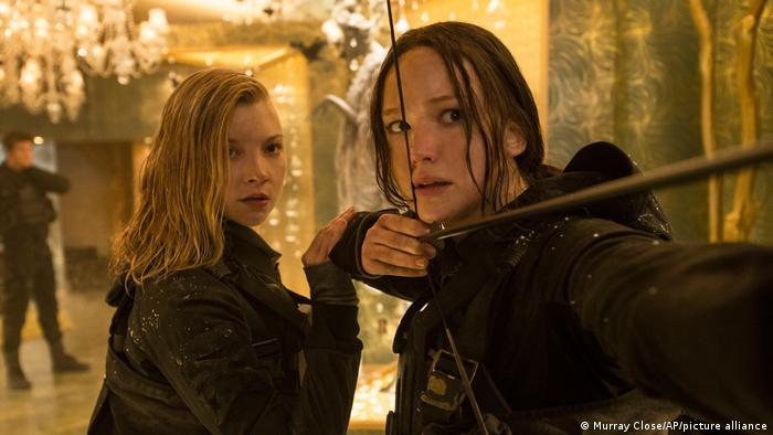 Film still 'The Hunger Games': Natalie Dormer as Cressida, left, and Jennifer Lawrence as Katniss Everdeen who is pulling a bow and arrow.