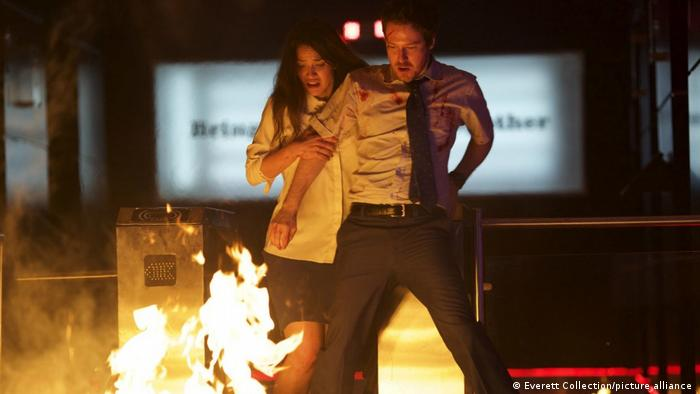 Film still 'The Belko Experiment' with a man and woman in front of a fire.