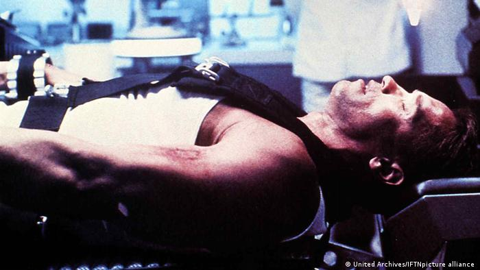Film still 'Running Man' with Arnold Schwarzenegger strapped onto a operating table.