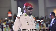 Guinea junta leader Colonel Mamady Doumbouya, raises his hand at his swearing in ceremony as president of country transion on October 1, 2021 in Conakry. - The head of the junta in Guinea, Colonel Mamady Doumbouya, was sworn in on Friday as president of this West African country for a period of transition of still unknown duration and content. (Photo by Cellou BINANI / AFP) (Photo by CELLOU BINANI/AFP via Getty Images)