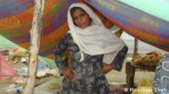 A widow waits in a makeshift tent