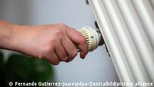 Eine Frau dreht am Thermostat einer Heizung in einer Wohnung.