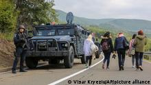 Ethnic Serbs walk past Kosovo police securing the area near the northern Kosovo border crossing of Jarinje on the ninth day of protest on Tuesday, Sept. 28, 2021. Ethnic Serbs in Kosovo have been blocking the border for a ninth straight day to protest a decision by Kosovo authorities to start removing Serbian license plates from cars entering the country, raising fears such incidents could unleash much deeper tensions between the two Balkan foes. (AP Photo/Visar Kryeziu)