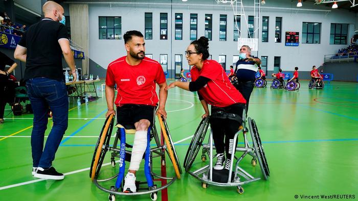 Afghan national women's wheelchair basketball team captain Nilofar Bayat and her husband Ramesh Naik Zai talk on the court ahead of their debut game in Spain