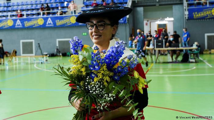 Nilofar Bayat, con un sombrero tradicional vasco, lleva flores en el campo después de su primer partido en España